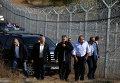 Премьер-министр Венгрии Виктор Орбан, слева, и его болгарский коллега Бойко Борисов, в центре, осматривают забор из колючей проволоки на границе от мигрантов.