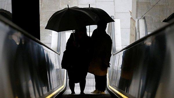Люди под зонтиком на эскалаторе. Архивное фото