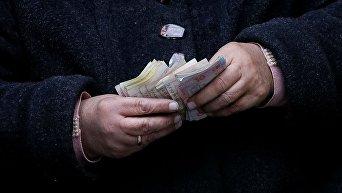 Пожилая женщина считает деньги в центре Львова