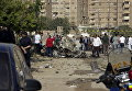 Египетские полицейские осматривают обломки автомобиля после того, как бомба взорвалась в столице Египте