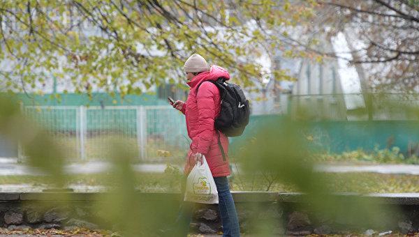 Женщина звонит по мобильному телефону на улице в Киеве