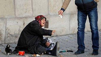 Пожилая женщина просит милостыню в центре Кишинева