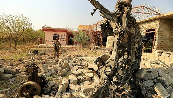 Член иракских сил безопасности осматривает обломки автомобиля, взорванного в ходе столкновений к югу от Мосула, Ирак.