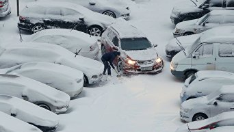 Мужчина убирает снег на парковке в Киеве