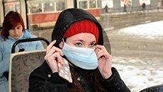 Девушка надевает маску в общественном транспорте. Архивное фото