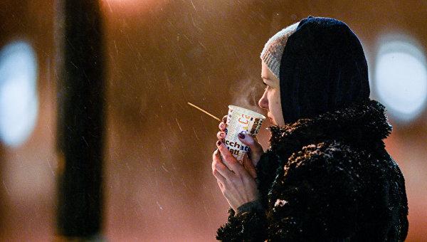 Девушка пьет кофе во время снегопада в Киеве