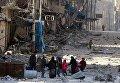 Сирийцы идут между обломками разрушенных зданий