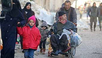 Люди с вещами готовятся к эвакуации из Алеппо