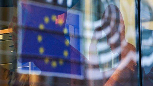 Отражение флага Евросоюза в окне одного из зданий в Брюсселе