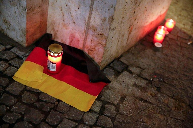 Свеча на флаге Германии у места ЧП в Берлине, где грузовик наехал на толпу людей
