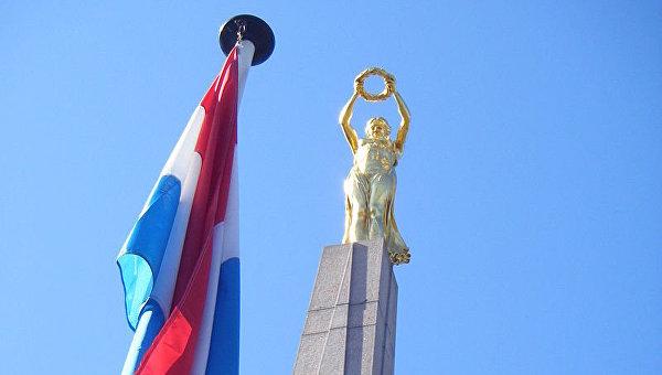 Государственный флаг Люксембурга у военного мемориала Gëlle Fra