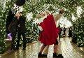Уличные исполнители, одетые как рождественские эльфы, танцуют под праздничными украшениями в центре Киева