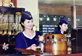 Молодая стюардесса, разливающая знаменитое местное пиво «Тэдонган».