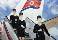 Три стюардессы стоят на трапе.