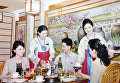 Ещё одно изображение показывает мужчину и двух женщин. одна из которых очень похожа на жену Ким Чен Ына, которых обслуживают две официантки.