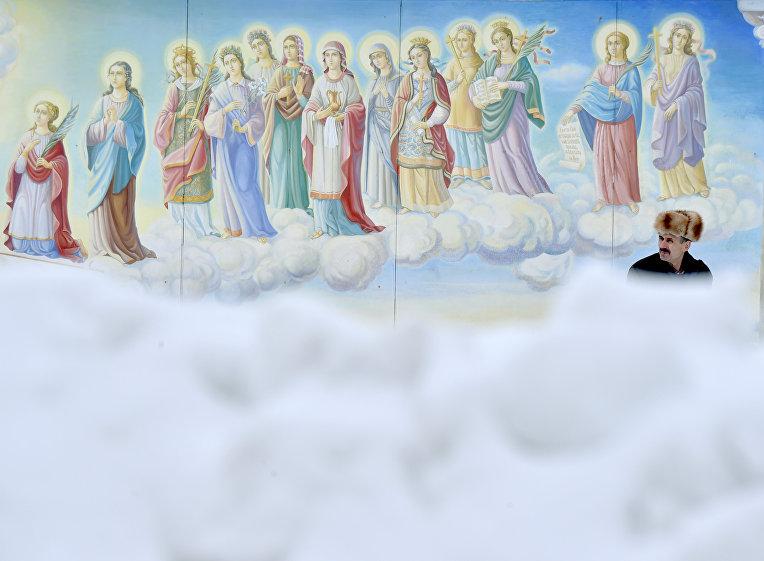 Мужчина за огромным сугробом снега смотрит на фрески Михайловского собора в Киеве