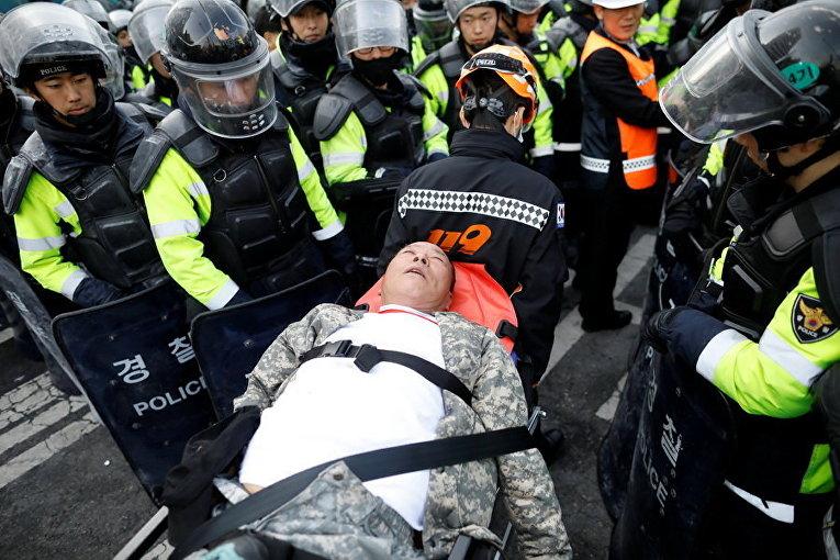 Пострадавший во время акции протеста сторонник президента Южной Кореи возле Конституционного суда в Сеуле