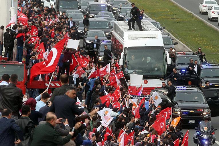 Президент Турции Реджеп Тайип Эрдоган и его супруга Эмине Эрдоган из автобуса приветствуют сторонников конституционного референдума.