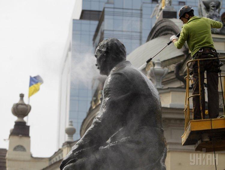 Работник коммунальных служб моет памятник композитору Николаю Лысенко в рамках акции Чистый день.