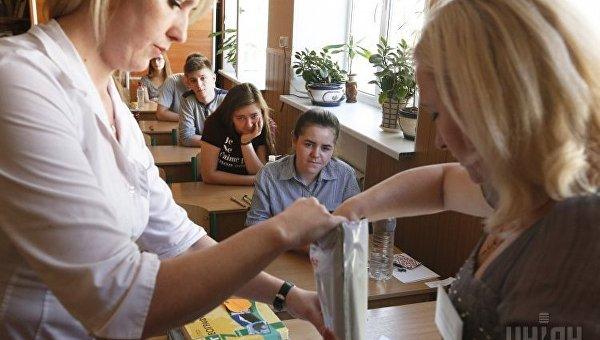 Инструкторы внешнего независимого оценивания (ВНО) открывают пакет с заданиями по математике в специализированной школе Шевченковского района в Киеве