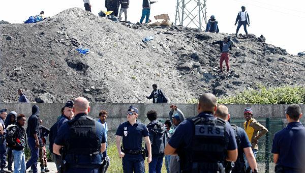 Французская полиция и мигранты в точке распространения продовольствия в Кале