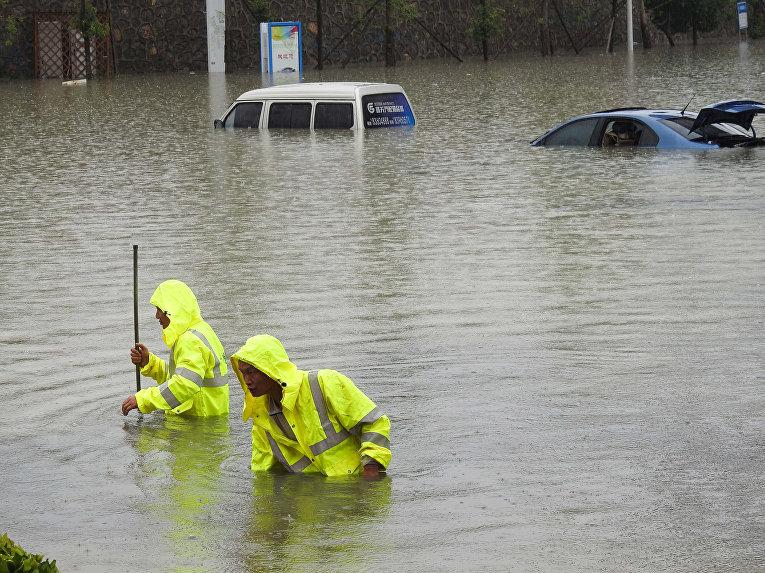 Рабочие открывают крышки люков для слива вод на затопленной улице после сильных осадков в городе Гуйян