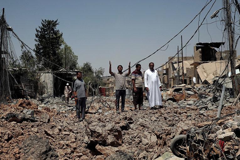 Гражданин поднимает руки к небу среди обломков возле линии фронта в западном Мосуле