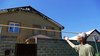 Мужчина у здания, поврежденного в результате обстрела, в Донецке