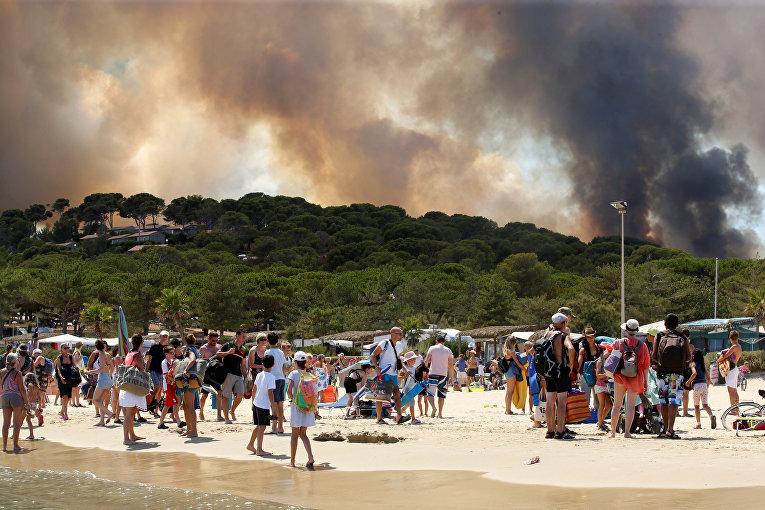 Туристы в спешке эвакуируются с пляжа из-за пожара на склоне в Борм-ле-Мимозасе в департаменте Вар, Франция.