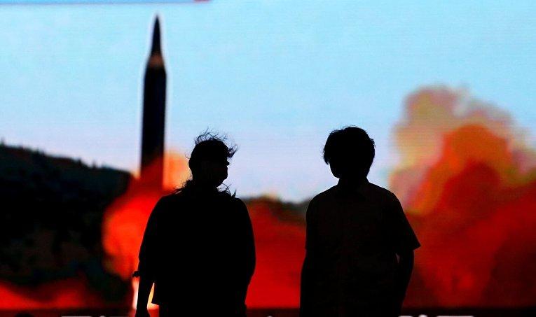 Японцы в Токио напротив монитора с новостями о ракетных испытаниях Северной Кореи