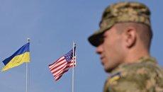Украинский военный на фоне флагов США и Украины