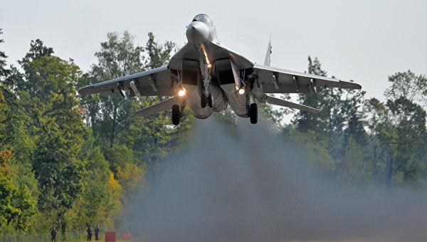Самолет МиГ-29 ВВС Белоруссии совершает пролет над аэродромным участком автодороги Минск-Могилев