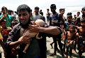 Беженец из Бангладеш со своим маленьким сыном, который утонул, когда перевернулась лодка с беженцами в Средиземном море.