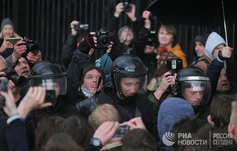 Сотрудники правоохранительных органов и фотографы на Тверской улице в Москве во время несанкционированной акции, 7 октября 2017