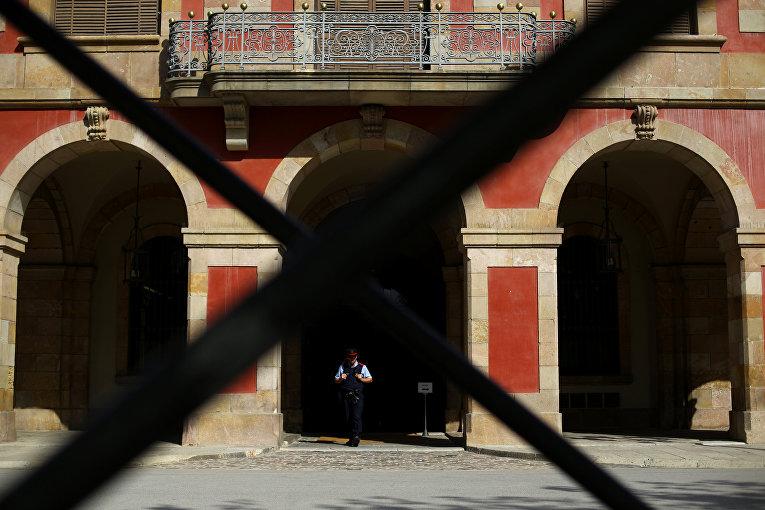 Сотрудник каталонской региональной полиции Моссос Д'эквадра охраняет здание регионального собрания Каталонии.