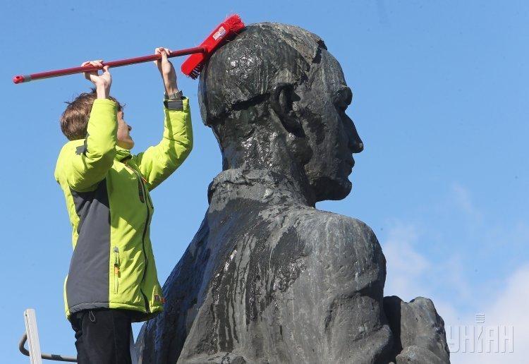 Студент Национального университета Киево-Могилянская академия моет памятник Григорию Сковороде во время традиционной акции Чистый Сковорода на Контрактовой площади в Киеве.