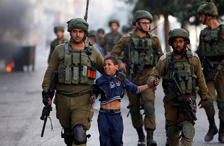 Израильские солдаты задерживают палестинского мальчика во время столкновений в городе Хеврон на Западном берегу.