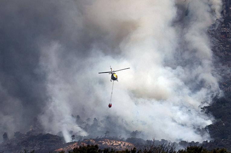 Вертолет тушит пожары в Кейптауне, Южная Африка.