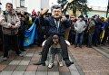 Ряженый в костюме президента Украины Петра Порошенко, который сидит на плечах у украинского казака, во время вече у здания Верховной Рады в Киеве