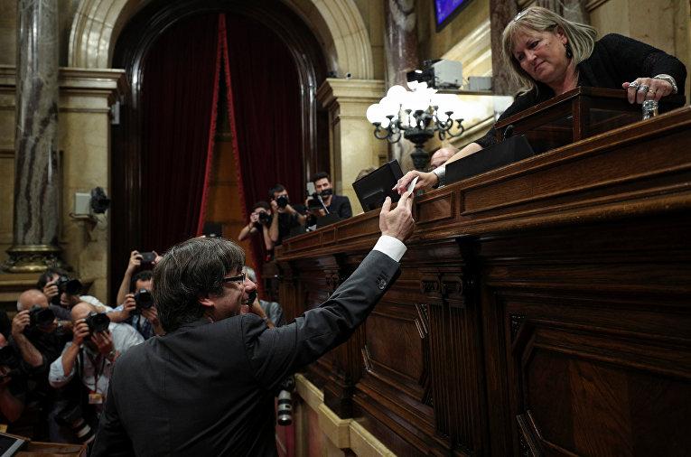 Глава Каталонии Карлес Пучдемон вручает свой бюллетень во время голосования по вопросу о независимости от Испании в региональном парламенте Каталонии в Барселоне