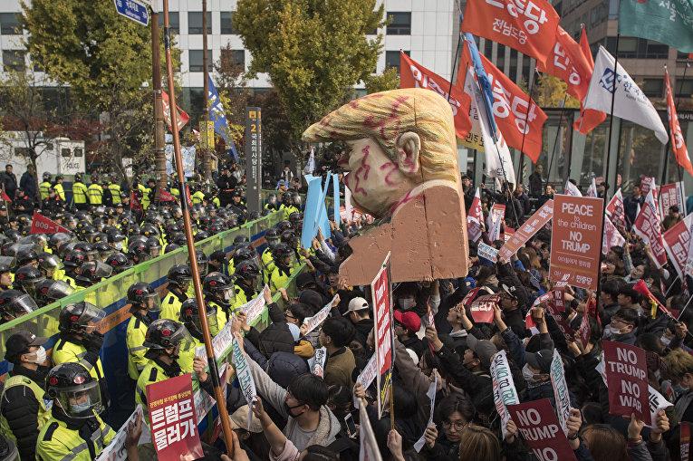 Протестующие в Сеуле держат огромный бюст Дональда Трампа. Выступая в Южной Корее он предложил лидеру КНДР Ким Чен Ыну путь к гораздо лучшему будущему.
