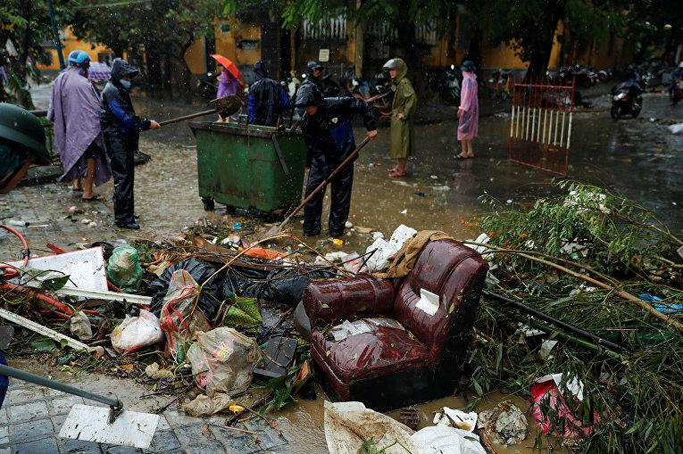 Вьетнамские полицейские убирают обломки после тайфуна Дамри, который нанес удар по древнему городу  Хой Ан (входит в список исторического наследия ЮНЕСКО)