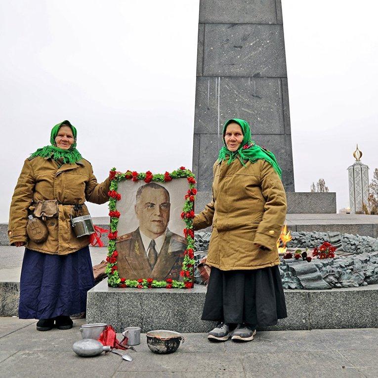Пожилые женщины с портретом маршала Жукова у памятника Вечный огонь в киевском Парке Славы