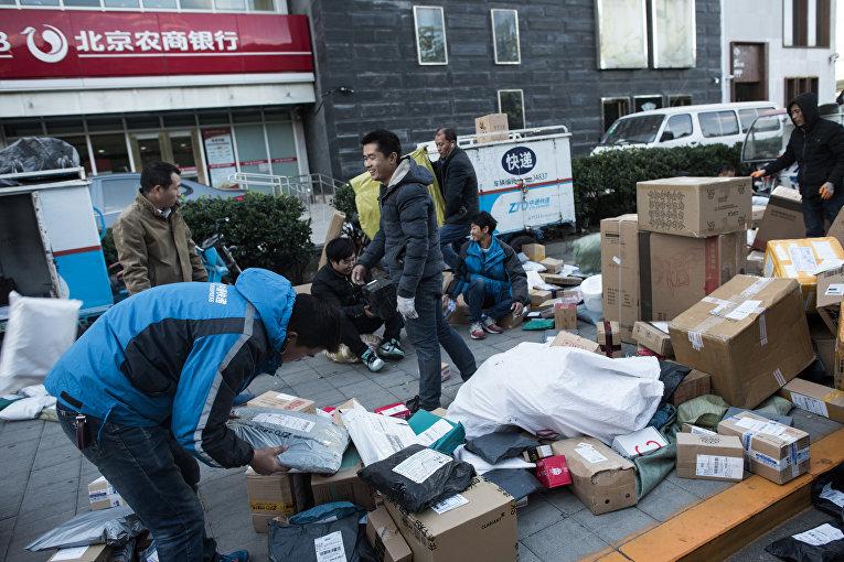 Почтовые рабочие в Пекине сортируют коробки с покупками, которые китайцы массово делают в канун Дня одиночек