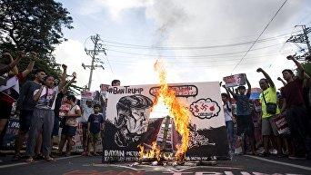 Протестующие сжигают антиамериканский баннер с лицом Дональда Трампа в канун начала саммита АСЕАН в Маниле