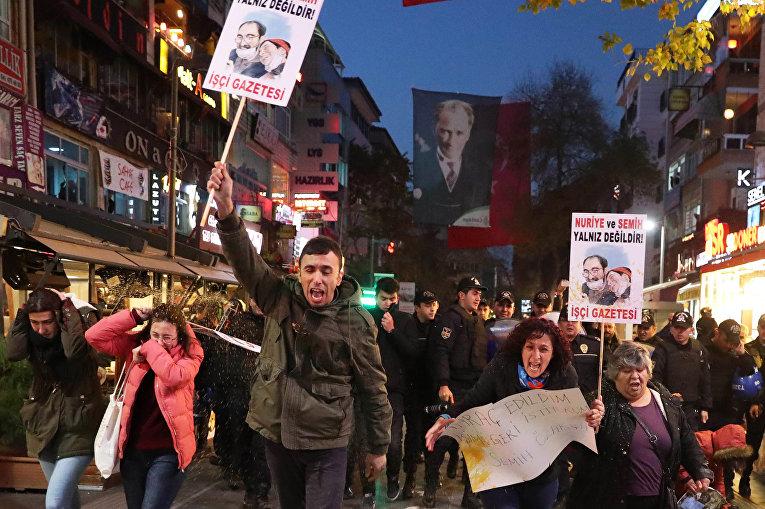 Протестующие поддерживают турецкого преподавателя Нурие Гульмена, который находится под арестом и объявил голодовку в тюрьме. Гульмена обвиняют в участии в антиправительственном мятеже