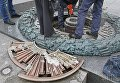 Коммунальщики очищают от цемента залитый Вечный Огонь в Киеве.
