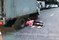 Китаянка чудом избежала смерти, попав под колеса грузовика. Видео