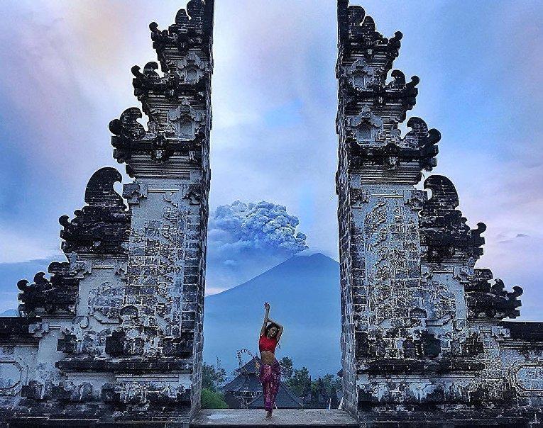 Туристы фотографируются на фоне проснувшегося вулкана Маунт Агунг на Бали