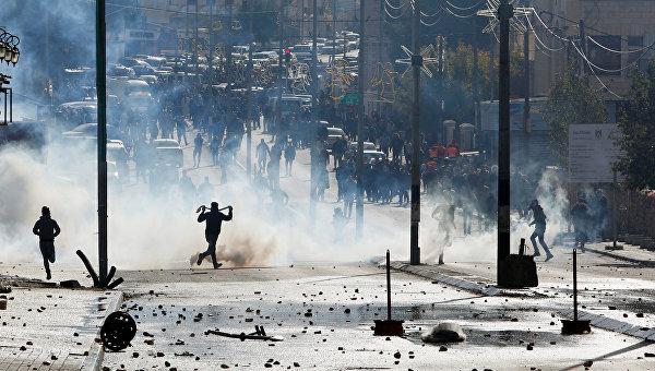 Палестинские протестующие бегут в укрытие от слезоточивого газа, во время столкновений израильскими войсками в знак протеста против решения президента США Дональда Трампа признать Иерусалим столицей Израиля в городе Вифлееме